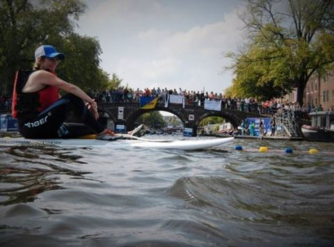 The Amsterdam City Swim: swimming in the canals, with rescue staff on a paddle board.