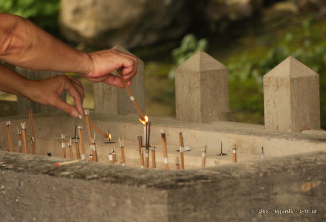 Worshippers burning incense at the sacred place of the Usuki stone Buddhas on Kyushu Island, Japan.