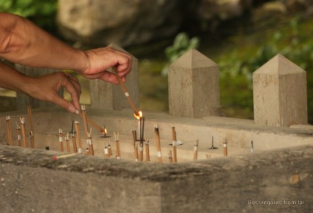 Worshippers burning incense at the sacred place of the Usuki stone Buddhas on Kyushu Island, Japan.