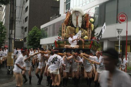 A large float dragged by Japanese men in traditional costumes through the streets of Fukuoka, Kyushu during the Hakata Gion Yamakasa festival