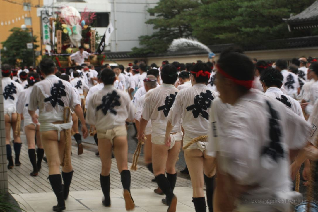A group of Japanese men wearing the traditional outfit walks in the street behind a large float during the festival in Fukuoka, Kyushu