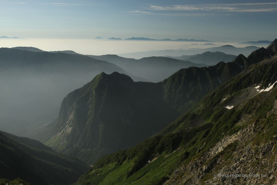 Islands of mountains in a sea of clouds, with Mount Fuji in the background, while hiking the Japanese Alps.