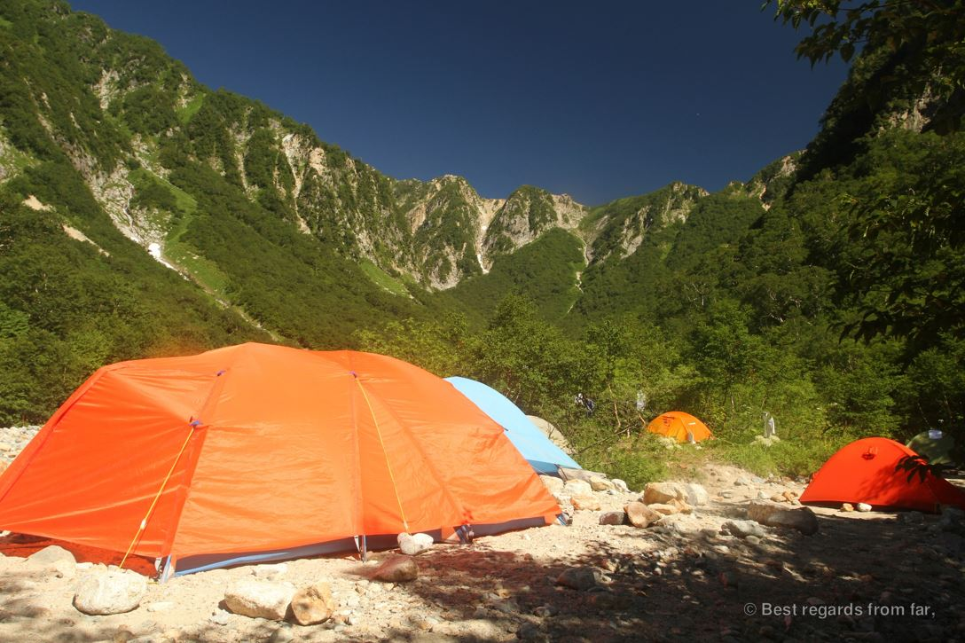 A high-altitude camp with colourful technical tents at the foot of the mountains, while hiking the Japanese Alps.