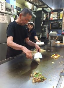 Japanese chef cooking Okonomiyaki, the savory pancakes on a hot griddle, at Okonomi-mura, Hiroshima, Japan