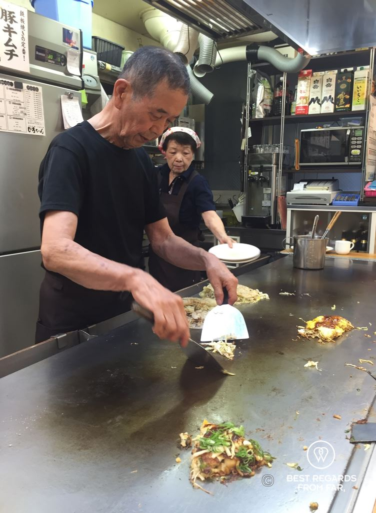 Japanese chef cooking Okonomiyaki, the savory pancakes on a hot griddle, at Okonomi-mura, Hiroshima, Japan