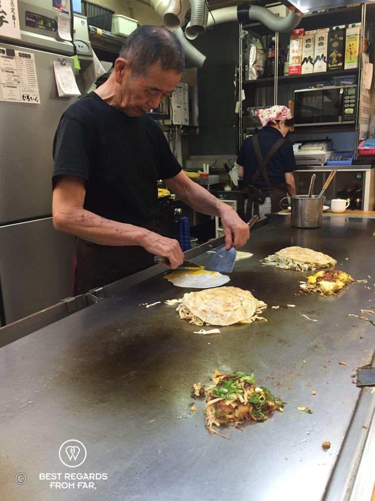 Japanese chef cooking Okonomiyaki, the savory pancakes, at Okonomi-mura, Hiroshima, Japan