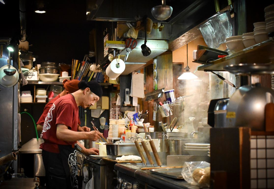 Japanese chef cooking ramen noodles at a ramen-ya in Japan