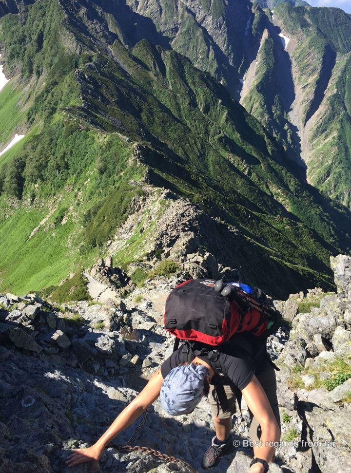 Hiker climbing up along the Daikiretto ridgeline hike in the Japanese Alps.