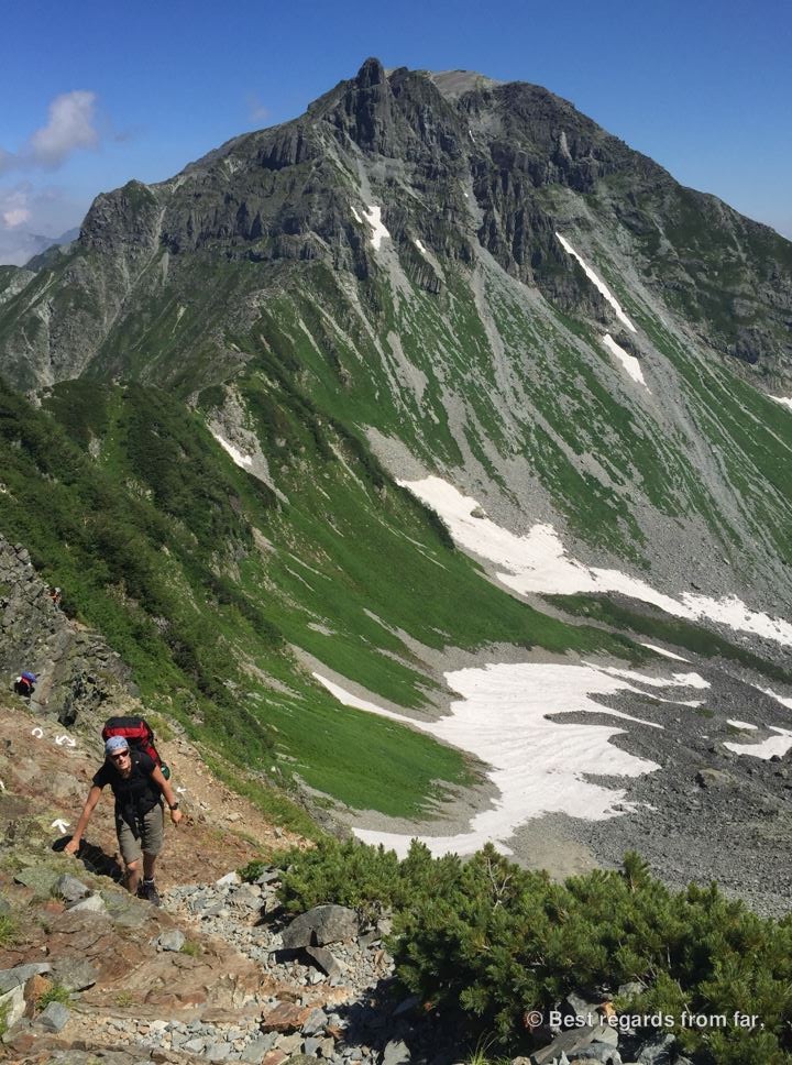 Hiker following the trail markers on the Daikiretto section while hiking the Japanese Alps. Mount Yari-dake in the background.
