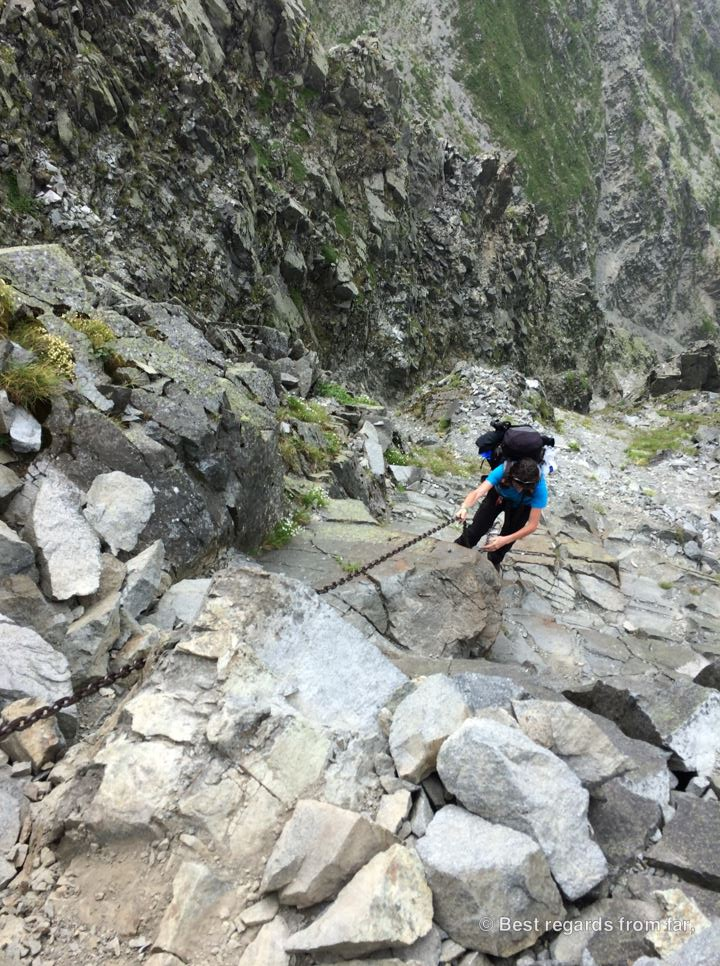 Hiker climbing up on the Daikiretto section using a long chain while hiking the Japanese Alps.
