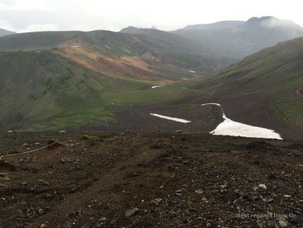 View on the Daisetsuzan Grand Traverse hiking trail covered in clouds and patches of snow, Hokkaido, Japan.