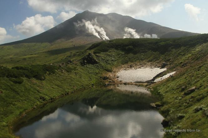 A lake and the active Asahi-dake volcano with its fumaroles in the Daisetsuzan National Park, Hokkaido Japan. The start of the Grand Traverse hike.