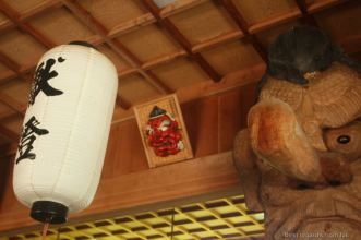 Woodcarved head with a big nose, white lantern with black Japanese letters in a shrine.