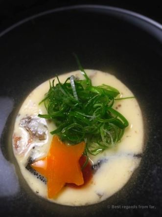 Steamed egg custard with shoft-shell turtle, floating in a transparant broth.