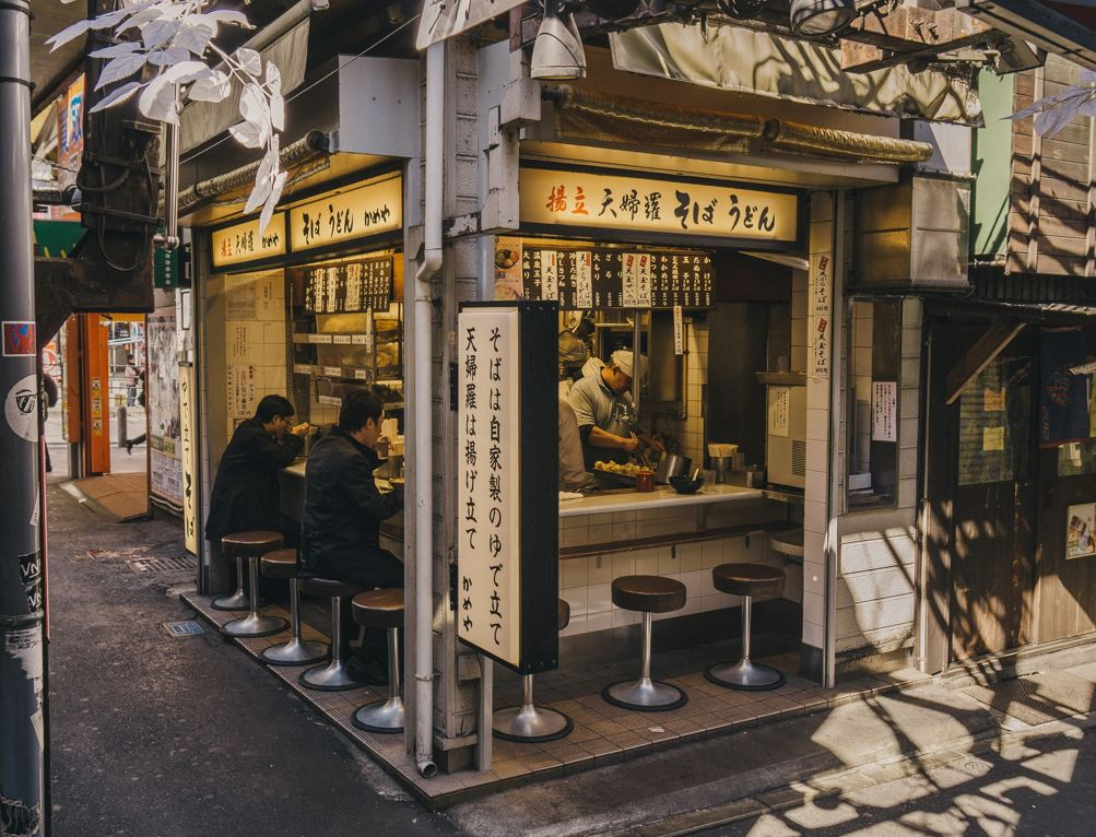 Two working men eating ramen noodles at a ramen-ya in Japan