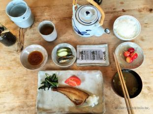 Delicious home-made breakfast with fermented soy beans, pickled vegetables, miso soup, fish and cherries.
