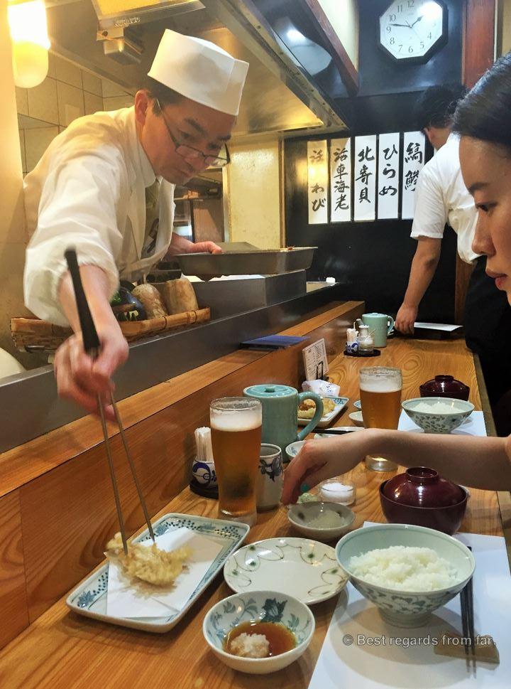 Tempura chef serving the tempura to a patron in a Japanese tempura-ya restaurant in Tokyo.