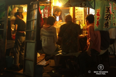 Yatai, or traditional food cart, in Fukuoka. Patrons sit at night while the chef is cooking.