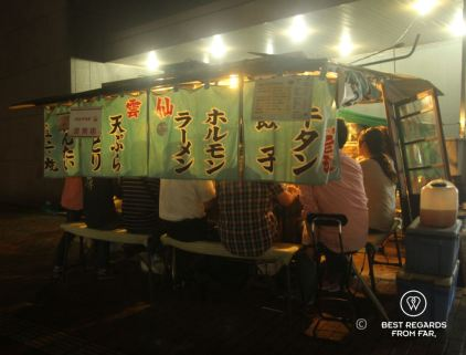 Yatai (food cart) in Fukuoka, Japan at night with patrons sitting