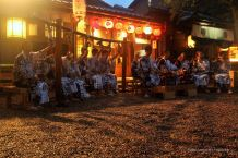 Monks in traditional outfits are playing musinc at night in fron of the Yasaka-jinja shrine in Kyoto, Japan