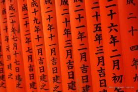 Dates engraved in the orange painted wood at Fushimi Inari Taisha