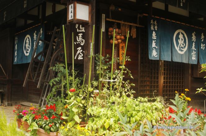 A traditional house in the Edo style. Blue flag with white Japanese characters, vegetables drying. Flowers in foreground Magome, Japan.