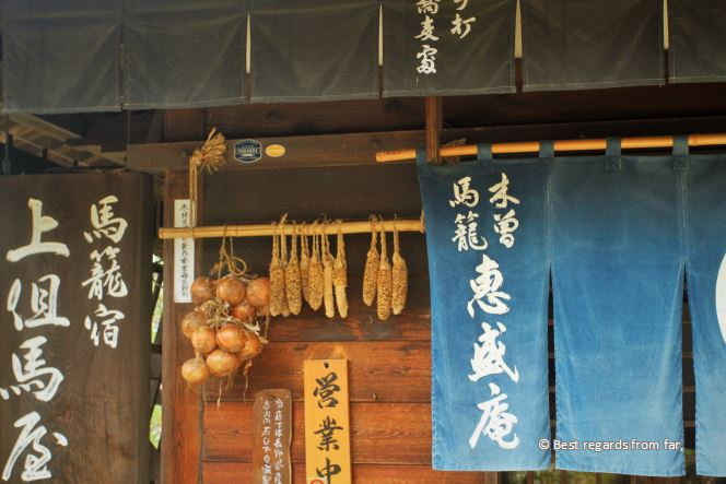 A traditional house in the Edo style. Blue flag with white Japanese characters, vegetables drying. Magome, Japan.