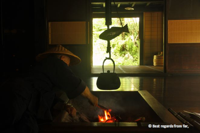 Japanese man with straw hat making tea above the fire in a traditional house.