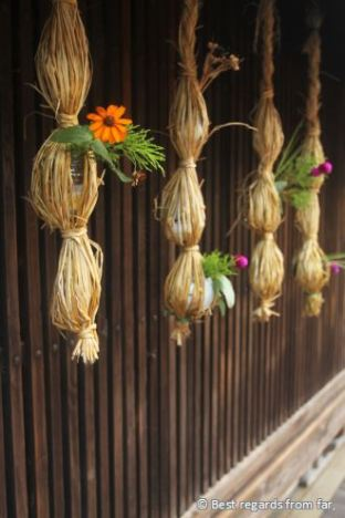 Wooden wall of a house with traditional decorations, flowers and ropes.
