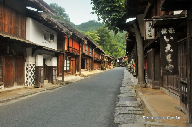 Barren street of Tsumago, white and black signboards with Japanese charcaters, trees.
