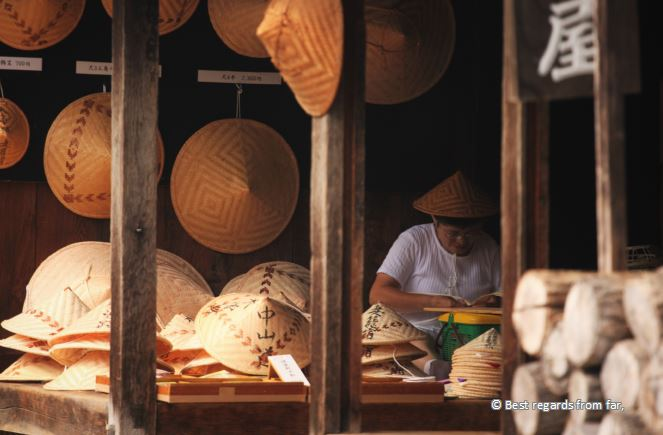 Woman with traditional hat crafting a Japanese hat.