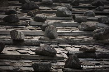Stones holding traditional wooden roofs, Tsumago, Japan.