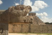 One of the many feathered snakes in Chichén Itza, with El Castillo in the background
