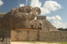 One of the many feathered snakes in Chichén Itza, with El Castillo in the background.