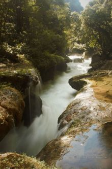 Under the limestone bridge with the pools passes the Cahabón River