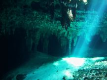 Sun rays peeping through the water and lighting up the cave