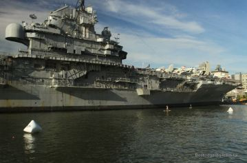 Two paddle boarders next to the U.S.S. Intrepid, New York City