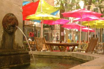 Typical square in Toulon with a fountain and colorful parasols, Toulon, French Riviera.