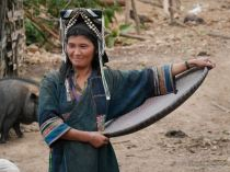 Morning chores of an Akha woman with her traditional headdress, Northern Laos