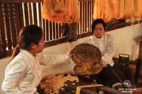Spinning the fine part of the golden silk cocoons separately, Siem Reap, Cambodia