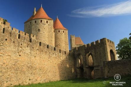 Medieval towers of Carcassonne with red roofs and the entrance gate to the castle over a moat filled with grass.