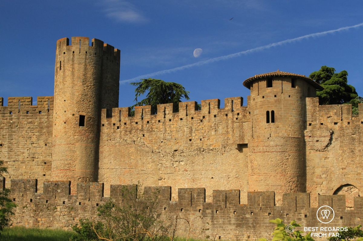 Roman and medieval ramparts, stone wall and towers from the Carcassonne Castle, blue skies and white moon.