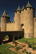 Bridge over a garden to enter the Comtal Castle of Carcassonne, blue skies and medieval towers.