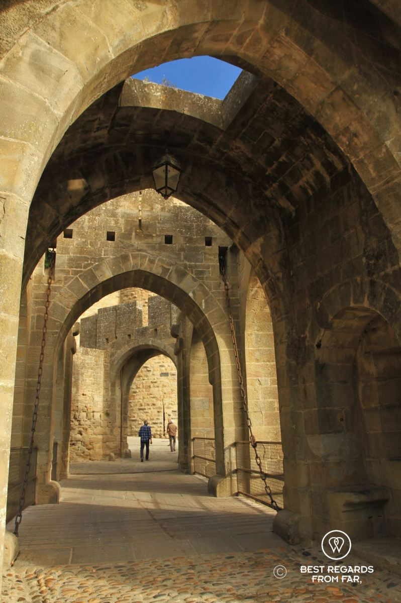 Medieval entrance of the Carcassonne Castle in France with a man walking through.