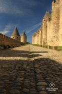 Straight empty coble ramparts with medieval towers and walls on both sides, Carcassonne, France.