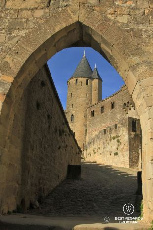 Medieval gate with cobble stoned street leading to a medieval tower in France.
