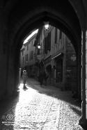 Black and white photo of a medieval gate, women walking through in a beam of sunlight.