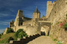 Woman walking through the Porte d'Aude in the medieval city of Carcassonne in France on a sunny day.