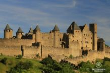 The medieval walled city of Carcassonne without people, on a hill, in the sun and with blue skies.