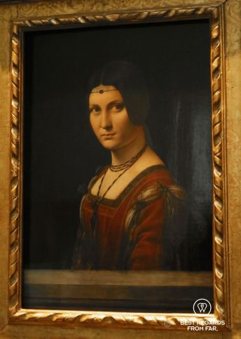 Painted portrait of a woman wearing a red dress. La belle ferronnière by Leonardo da Vinci, 1495-1499, Louvre Abu Dhabi, UAE.